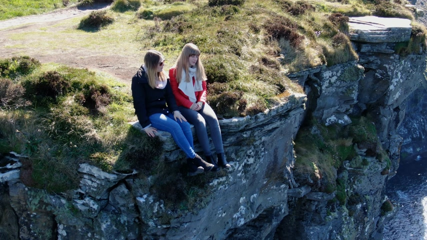 eire : Two girls sit on the edge of the famous Cliffs of Moher in Ireland Stock Footage