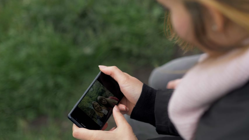 eire : Girl watches photos on her mobile phone