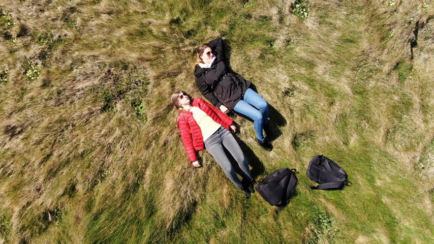 eire : Two women lying at the edge of the cliff at the Irish west coast - aerial drone footage Stock Footage