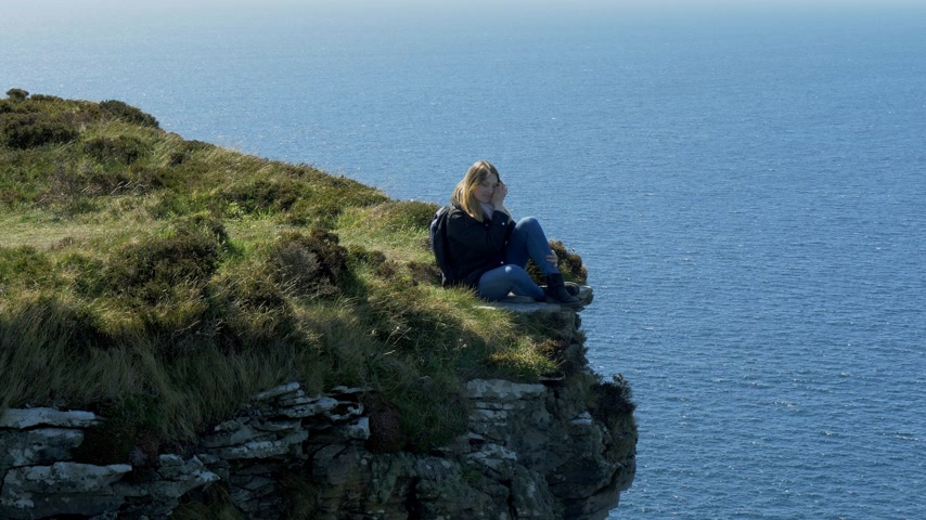 impacto : Young woman sitting on the edge of a cliff at the Irish west coast