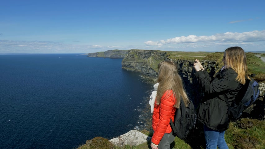 eire : Two young women enjoy the panoramic view at the Cliffs of Moher in Ireland