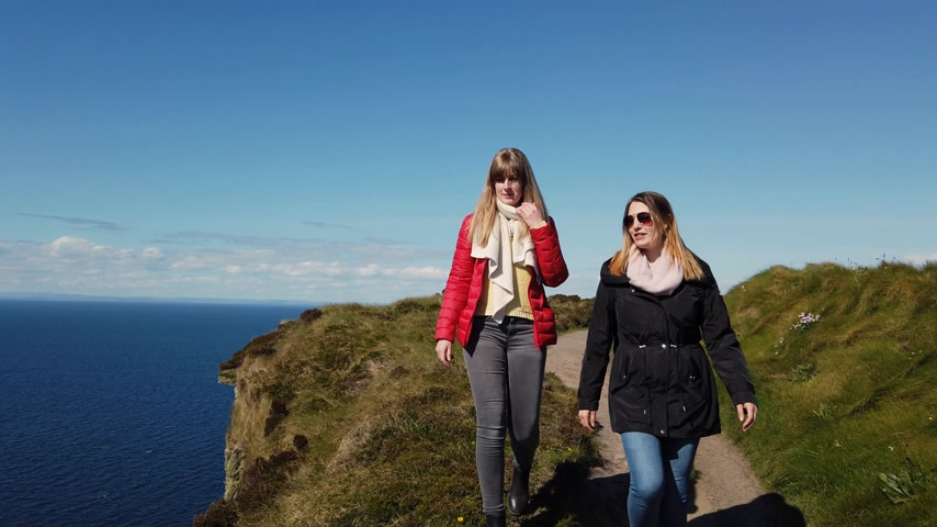 eire : Two girls walk along the edge of the famous Cliffs of Moher