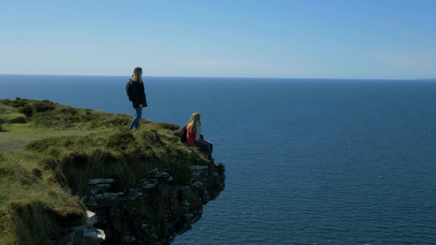 eire : Young woman sitting on the edge of a cliff at the Irish west coast
