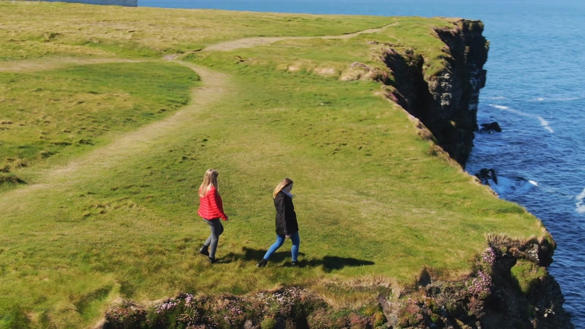 eire : Two girls in Ireland walk on the edge of the cliffs Stock Footage