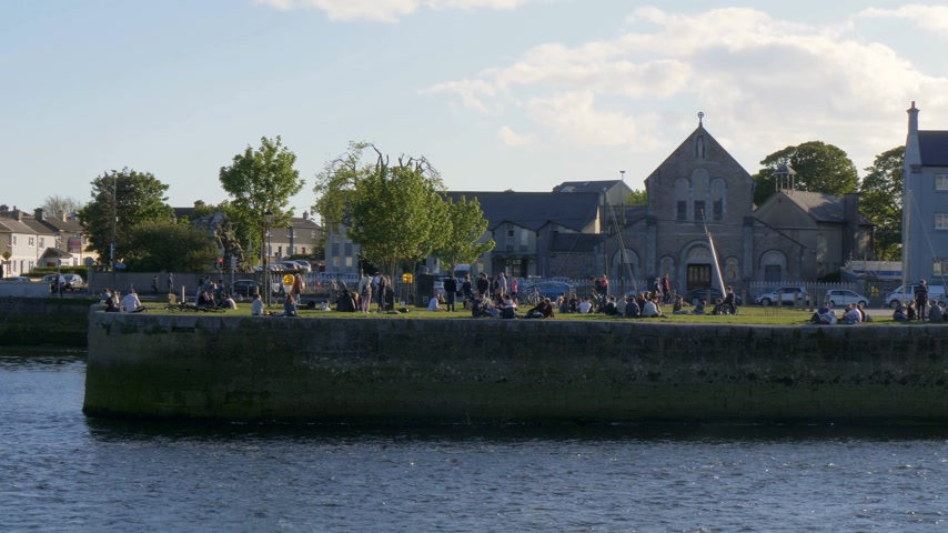 v řadě : Young people relax at Galway Claddagh on a sunny day - GALWAY, IRELAND - MAY 11, 2019 Dostupné videozáznamy