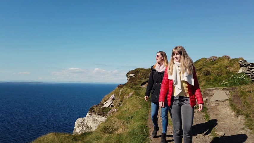 západ : Two girls walk along the edge of the famous Cliffs of Moher