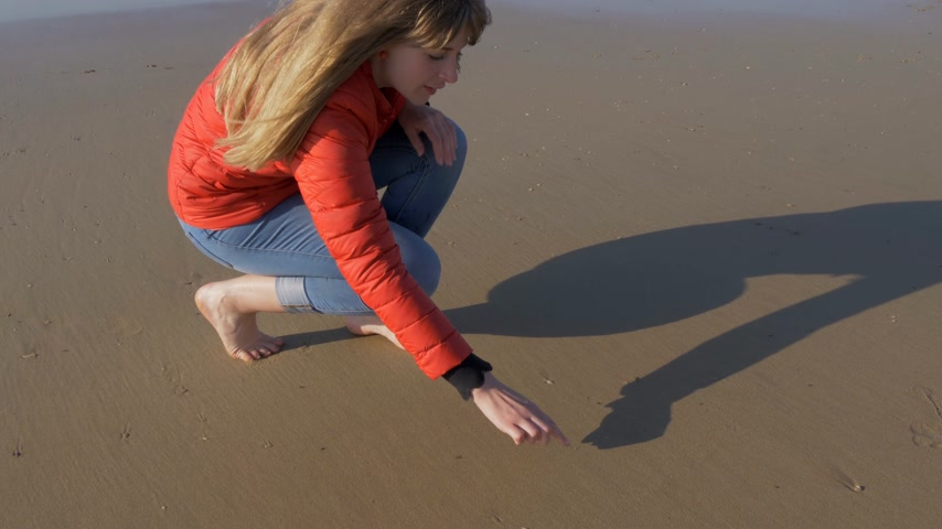 vertente : Girl writes a heart symbol in the sand on a beach