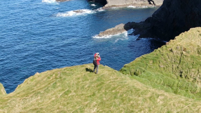 yarımada : Two girls in Ireland walk on the cliffs of Kilkee on a sunny day - aerial drone view Stok Video