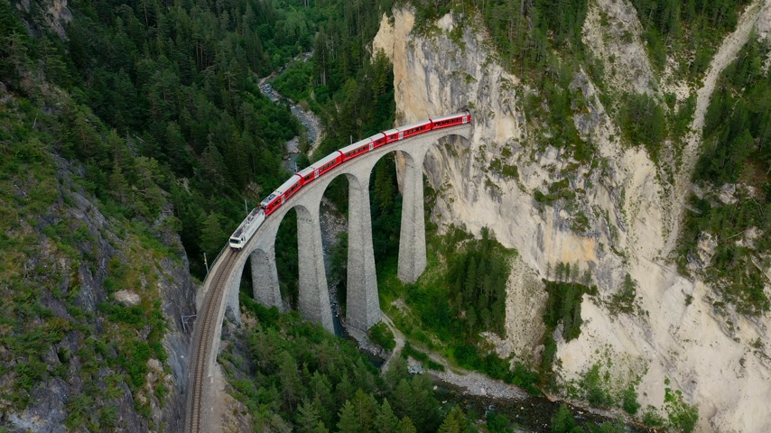 švýcarský : Glacier Express train on the famous viaduct in Switzerland - aerial view