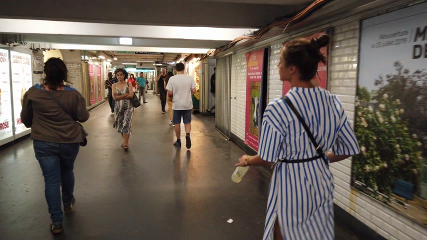 french metro : Young woman walks through a Paris Metro station - PARIS, FRANCE - JULY 29, 2019