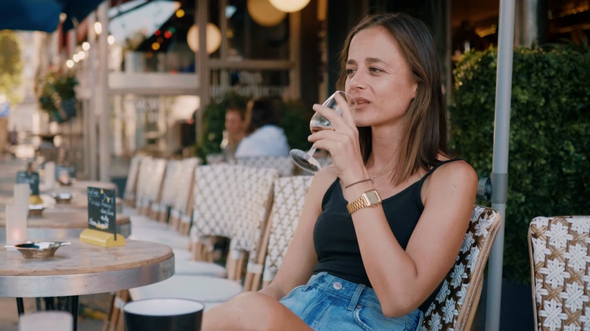 parisli : French girl drinks a glass of wine at a street cafe in Paris Stok Video