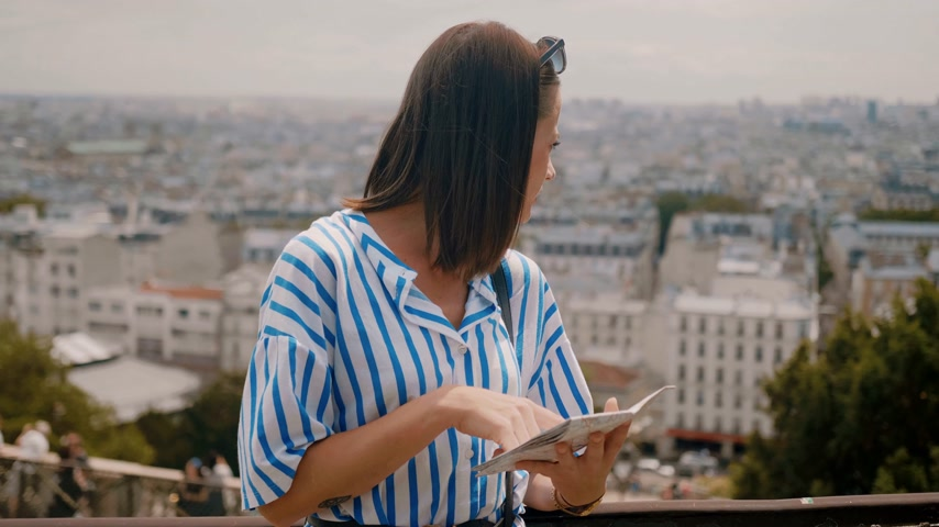 パリ : Young woman in Paris checks destinations on the map