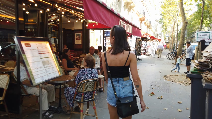 parisli : Young French woman walks through the city of Paris - PARIS, FRANCE - JULY 29, 2019 Stok Video