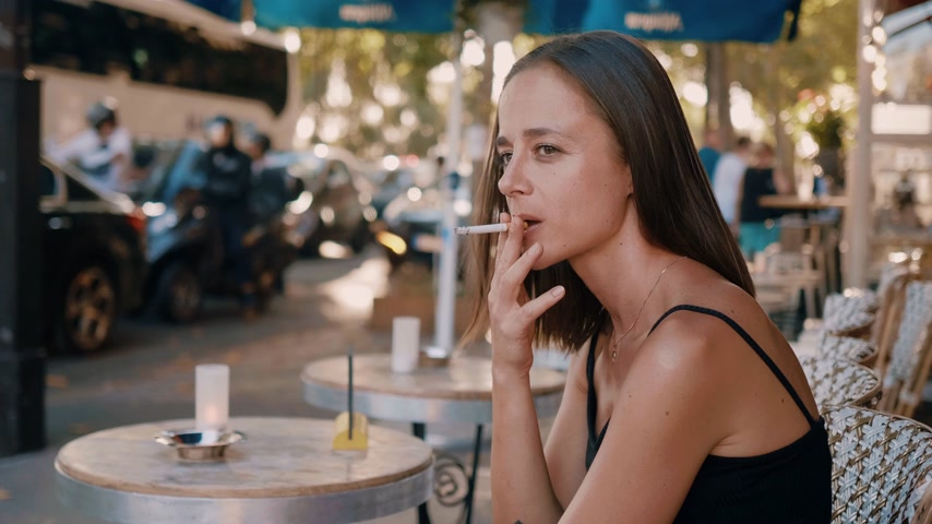 parigino : Young French woman smokes a cigarette while sitting in a street cafe in Paris