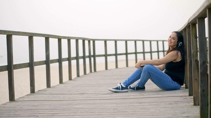 portugália : Young woman sits on a wooden pier at the beach
