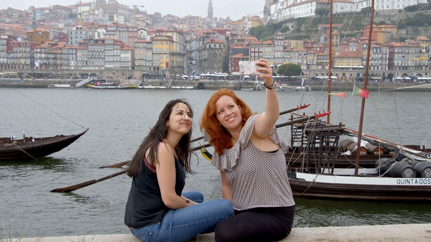 portugál : Tow girls in Porto take selfies at River Douro - CITY OF PORTO, PORTUGAL - SEPTEMBER 18, 2019