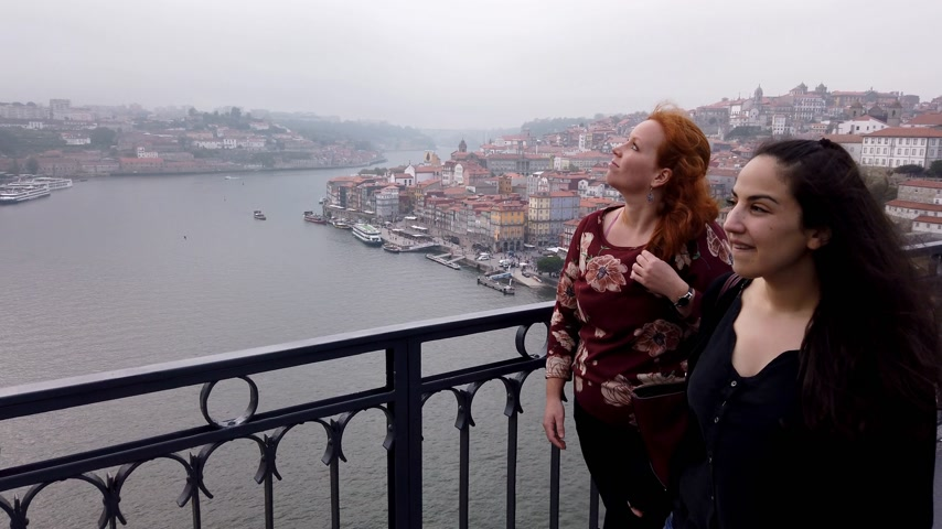 portugál : Two women on Dom Luis Bridge in Porto - CITY OF PORTO, PORTUGAL - SEPTEMBER 18, 2019 Stock mozgókép