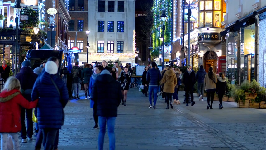 detailhandel : mensen lopen 's avonds in Covent Garden - LONDEN, ENGELAND - 10 DECEMBER 2019 Stockvideo