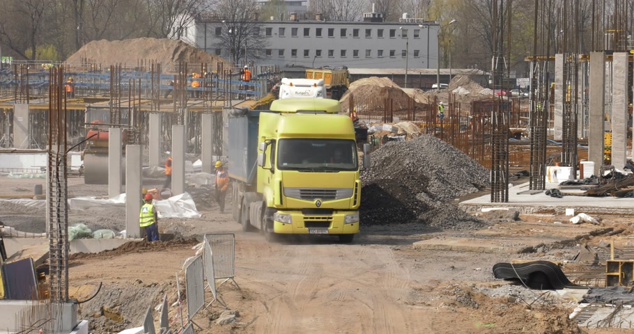 katowice : Poland, Katowice, April 2017:     Great shopping center construction. Workers are working. The truck unloads aggregate, stones and steel.    Closeup Wideo