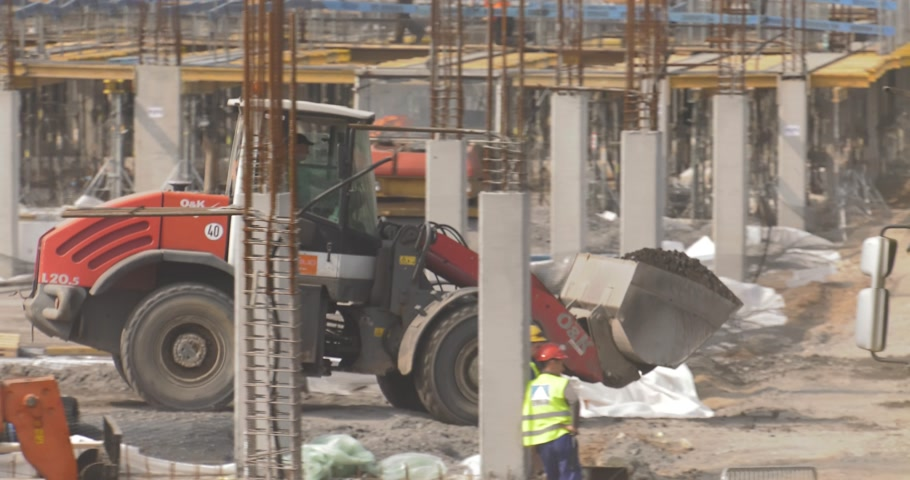 katowice : Poland, Katowice, April 2017:     Great shopping center construction.Workers are working.Backhoe loaders carry stones on site.The bulldozer goes forward.    Panning camera, Pan, Closeup