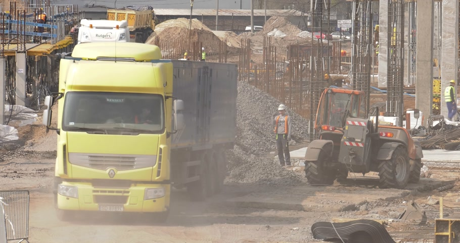 katowice : Poland, Katowice, April 2017:     Great shopping center construction. Workers are working. The truck unloads aggregate, stones and steel. The manager helps.    Closeup Wideo