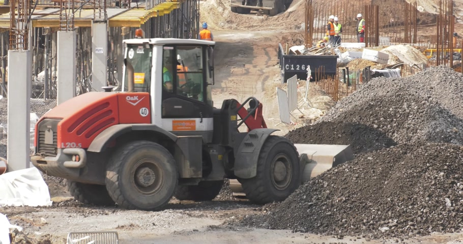 katowice : Poland, Katowice, April 2017:     Great shopping center construction.Workers are working.Backhoe loaders carry stones on the construction site.Bulldozer goes forward.    Panning camera, Pan, Closeup Wideo