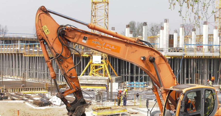 katowice : Poland, Katowice, April 2017:     A large orange excavator moves around a large construction site. Workers in the background.    Panning camera, Pan, Closeup