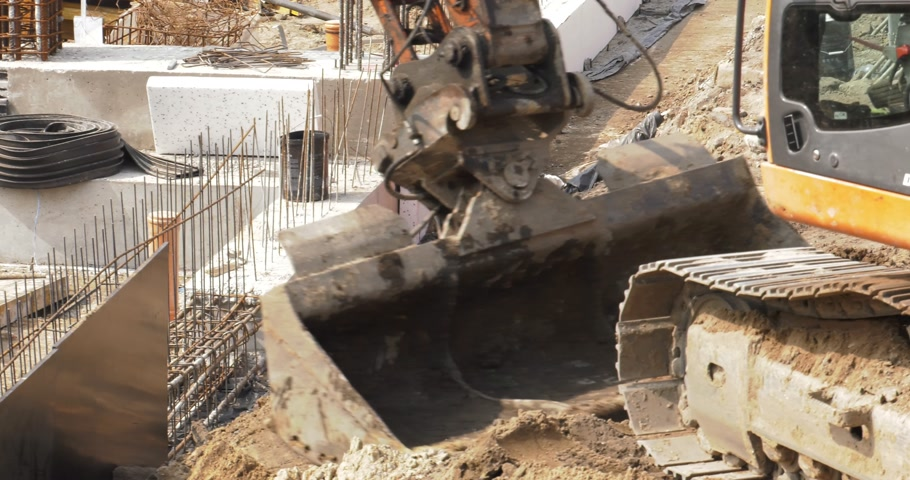 katowice : Poland, Katowice, April 2017:     A large orange excavator moves around a large construction site. Workers in the background. He loads a bucket of sand.    Closeup Wideo