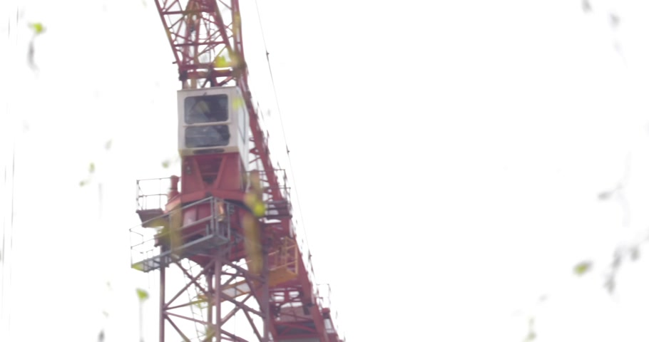 katowice : Poland, Katowice, April 2017:     On the construction site, the crane service is sitting in the capsule at the top. The crane moves. Blur on the leaves of a tree. Early spring.    Closeup