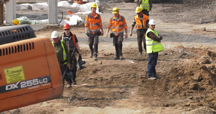katowice : Poland, Katowice, April 2017:     On the construction site many workers leave the area. End of work. Break at work. The rest are working.    Panning camera, Pan, Closeup