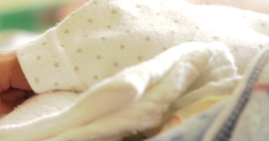 neonatology : 4K,    Small child, newborn in hospital at intensive care neonatal ward. ICE, CCU, ICU, ITU. Premature moving his hands and fingers.    Panning camera, Pan, Closeup