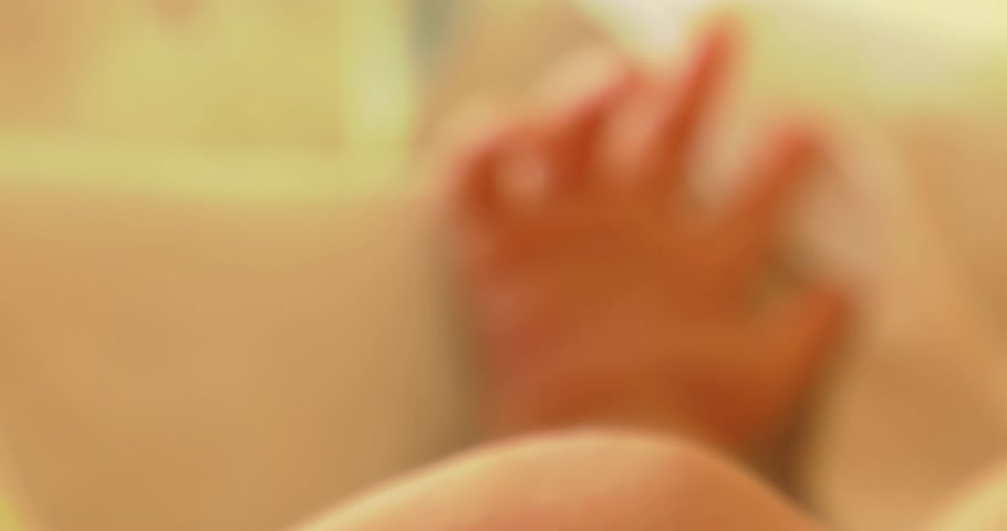 neonatology : 4K,    Little neonatal incubator, intensive hospital therapy: ICU, CCU, ICU, ITU. Tiny baby, small child, moving hands and fingers.    Panning camera, Pan, Closeup, Fade in out