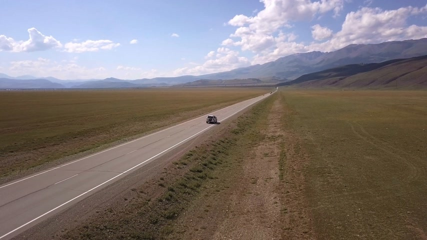 verhuizen : Aerial view of a gray car riding along the highway through the flat fields. In the background rise the slopes of the Altai mountains. Russia Cinematic video of driving a car far from the camera through the fields in the daytime.