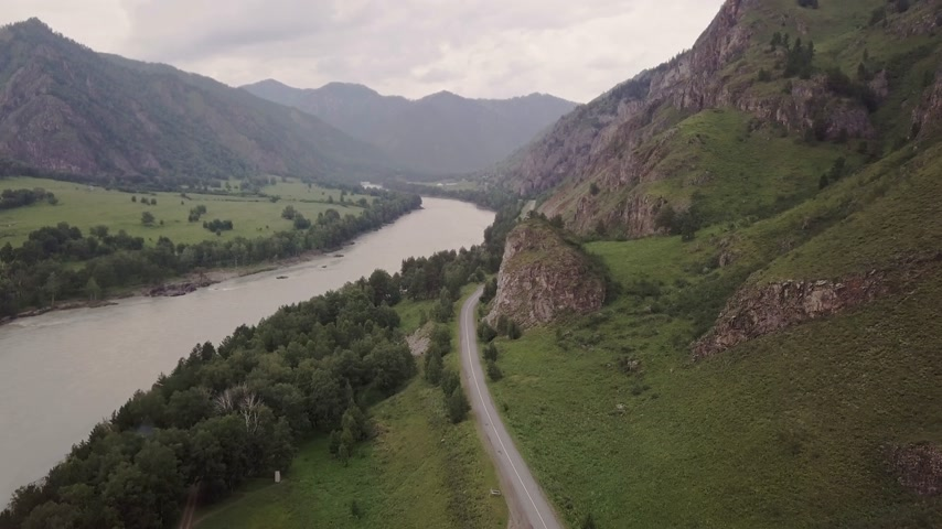 jasper : Beautiful views of the river from a birds flight on a cloudy day. Cars passing on the road. Scandinavian houses stand on the banks of the river
