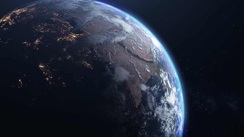 Space view of the planet Earth. Sunlight gradually fills the surface of the planet, changing night to day. Bright night lights of cities are replaced by cloudy day views. 動画素材