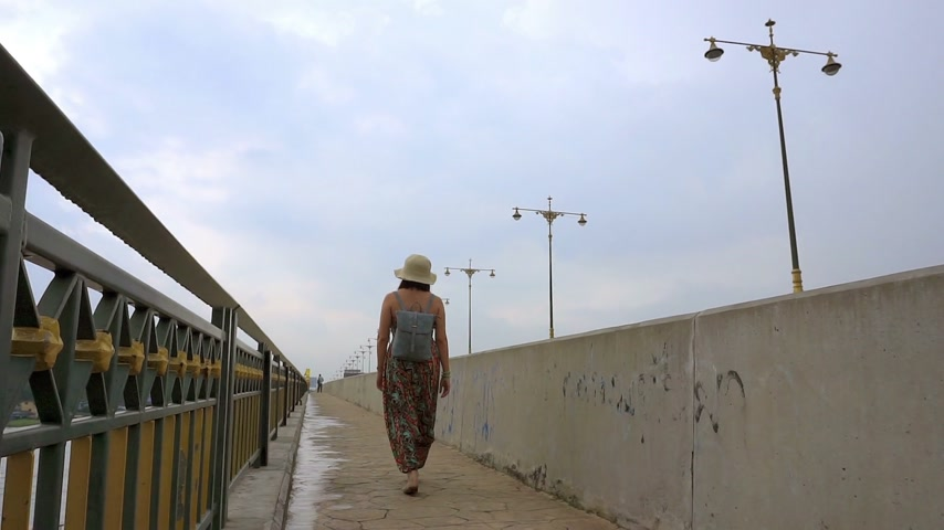 Women crossing the concrete bridge. (Panning shot)