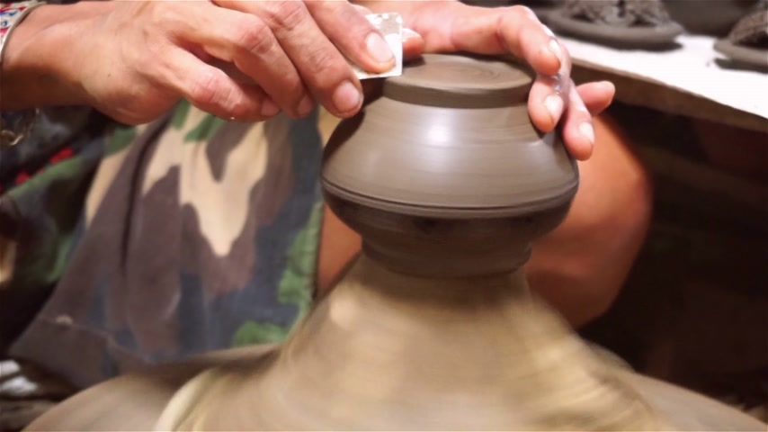The potter is molding the clay pot