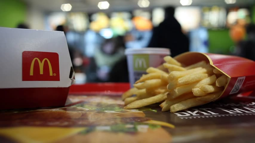 franczyza : Minsk, Belarus, March 20, 2018: Big Mac Box with McDonalds logo and French fries on a blurry background of people ordering food in McDonalds Restaurant