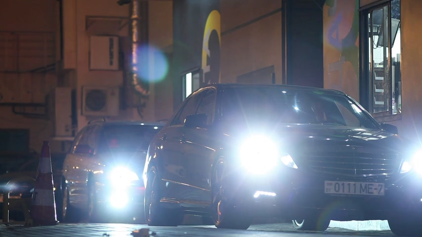 só : Minsk, Belarus, April 17, 2018: Customer receiving order from McDonalds drive thru service. Cars with headlights on rainy dusk buying food and leaving. Stock Footage