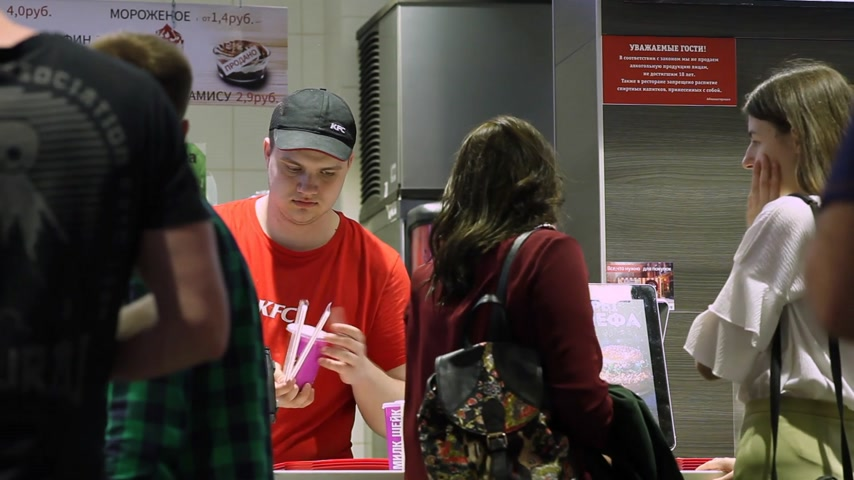 franczyza : Minsk, Belarus, May 3, 2018: A restaurant worker gives an order to visitors in KFC Restaurant