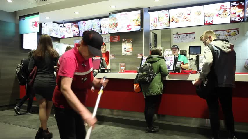 franczyza : Minsk, Belarus, April 4, 2018: People order food in a KFC Restaurant. Restaurant worker washes floor. Wideo