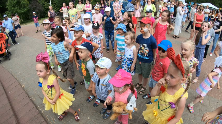 concert crowd : Minsk, Belarus, June 3, 2018: Little grateful spectators staring entertainment program  have fun and dance in park outdoors Stock Footage