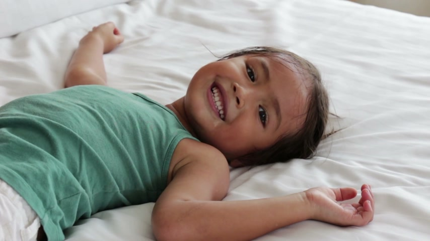 výraz : young little girl rolling playing on bed Dostupné videozáznamy
