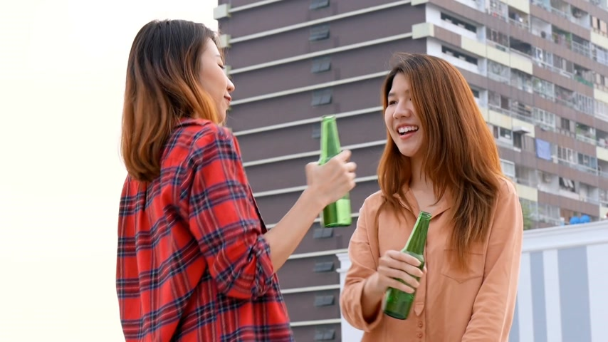 veranda : Young asian woman lesbian couple dancing and clinking bottles of beer party on rooftop.