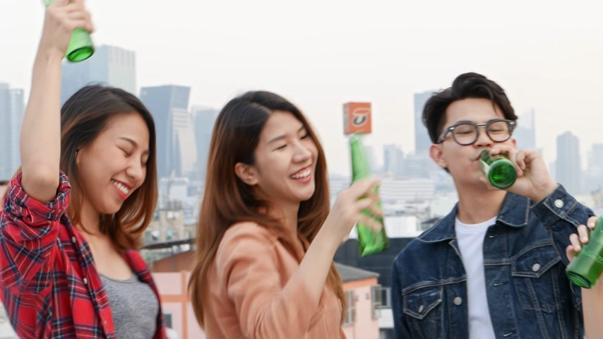 hipster : Group of Asian young people clinking bottles of beer party on rooftop.