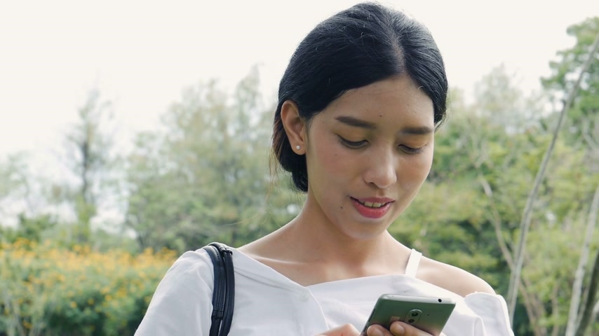 Beautiful asian young woman shot surfing the net online. Using mobile phone send text messaging at public park. Стоковые видеозаписи