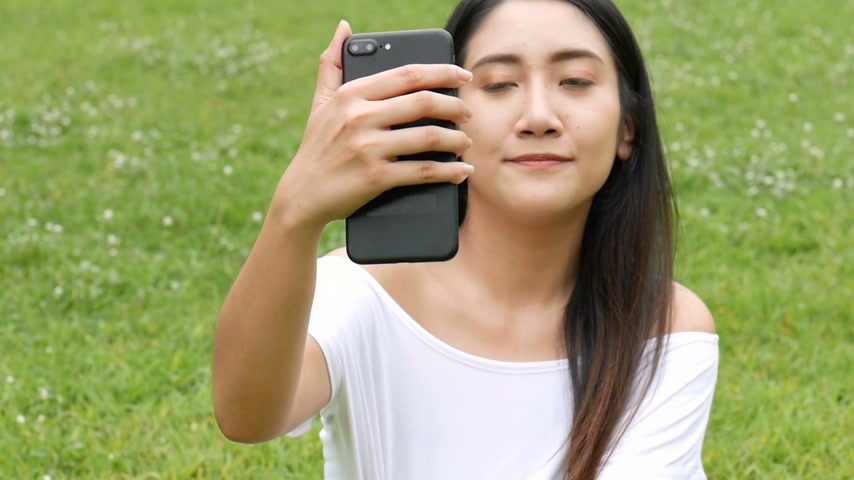 Beautiful asian young woman taking photo selfie using smart phone at public park. Slow motion filmed.