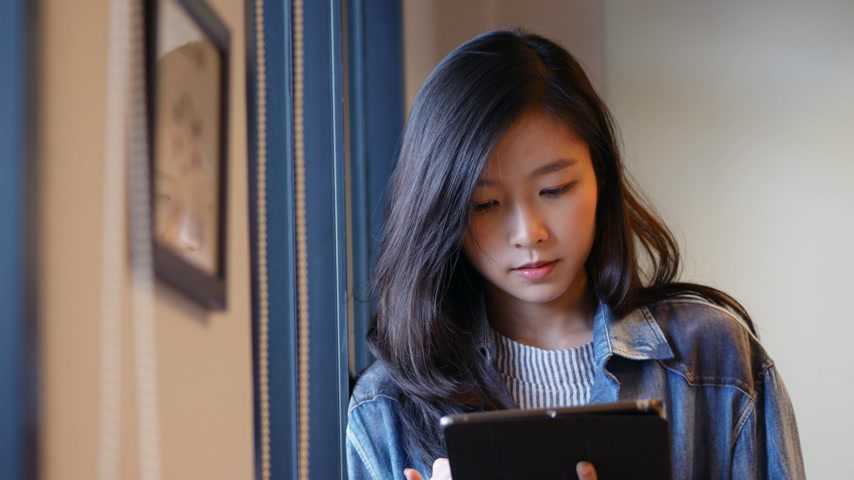 Young asian woman using tablet beside window at office.