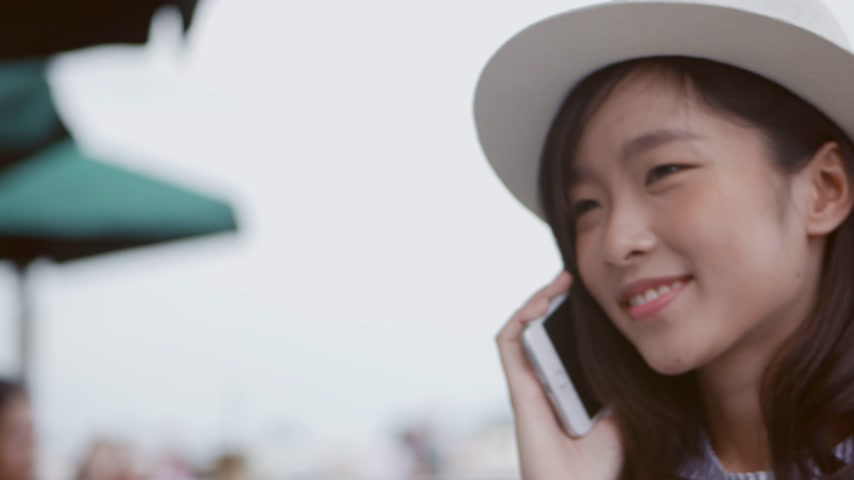 Young asian woman talking on phone at coffee shop. Beautiful young female asian caucasian model.