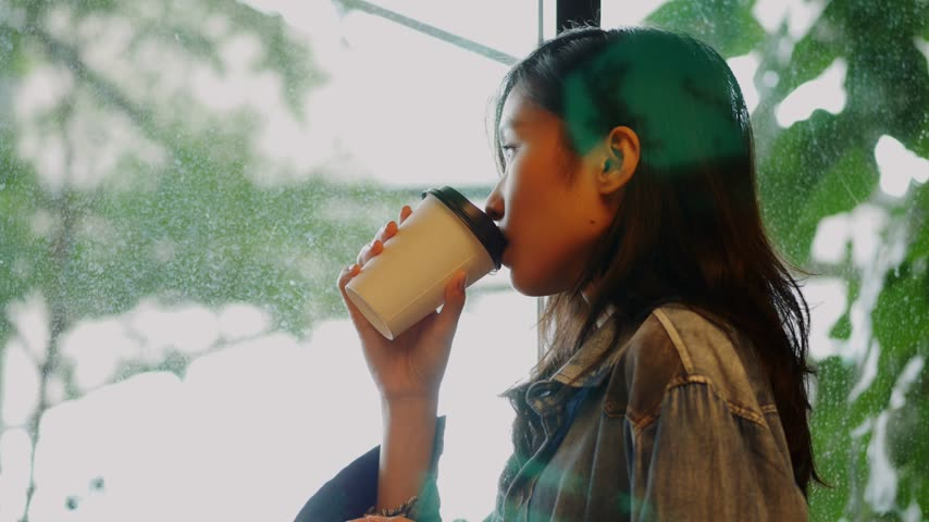 Businesswoman drinking coffee looking outside window at office. Young asian girl standing inside meeting room and hand holding coffee cup.